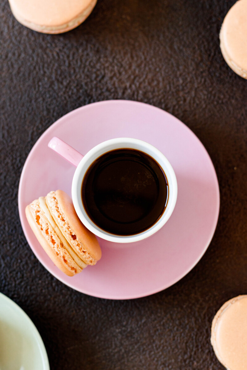 top view of a shot of Cuban coffee in a pink espresso mug sitting on a pink saucer with a cuban coffee macaron balanced alongside
