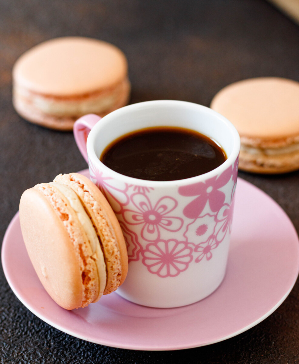 close up angled picture of the macaron alongside the shot of espresso in a pink floral cup on a pink saucer