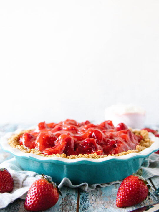 whole fresh strawberry pie in a blue pie dish on a mottled blue surface