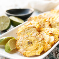 plated air fryer tostones on a rectangular white plate with lime wedges ready to enjoy