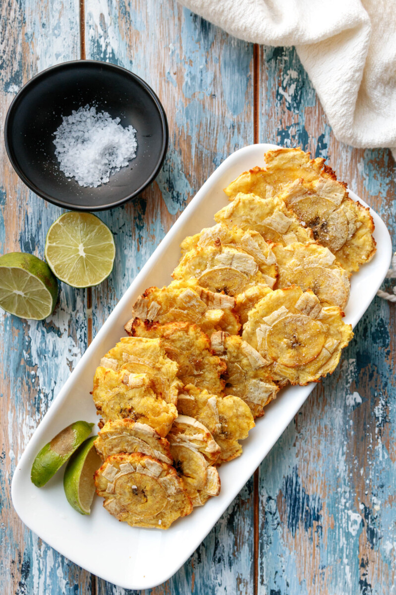 top view of the tostones on a mottled blue background with a dish of salt and cut lime as garnishes