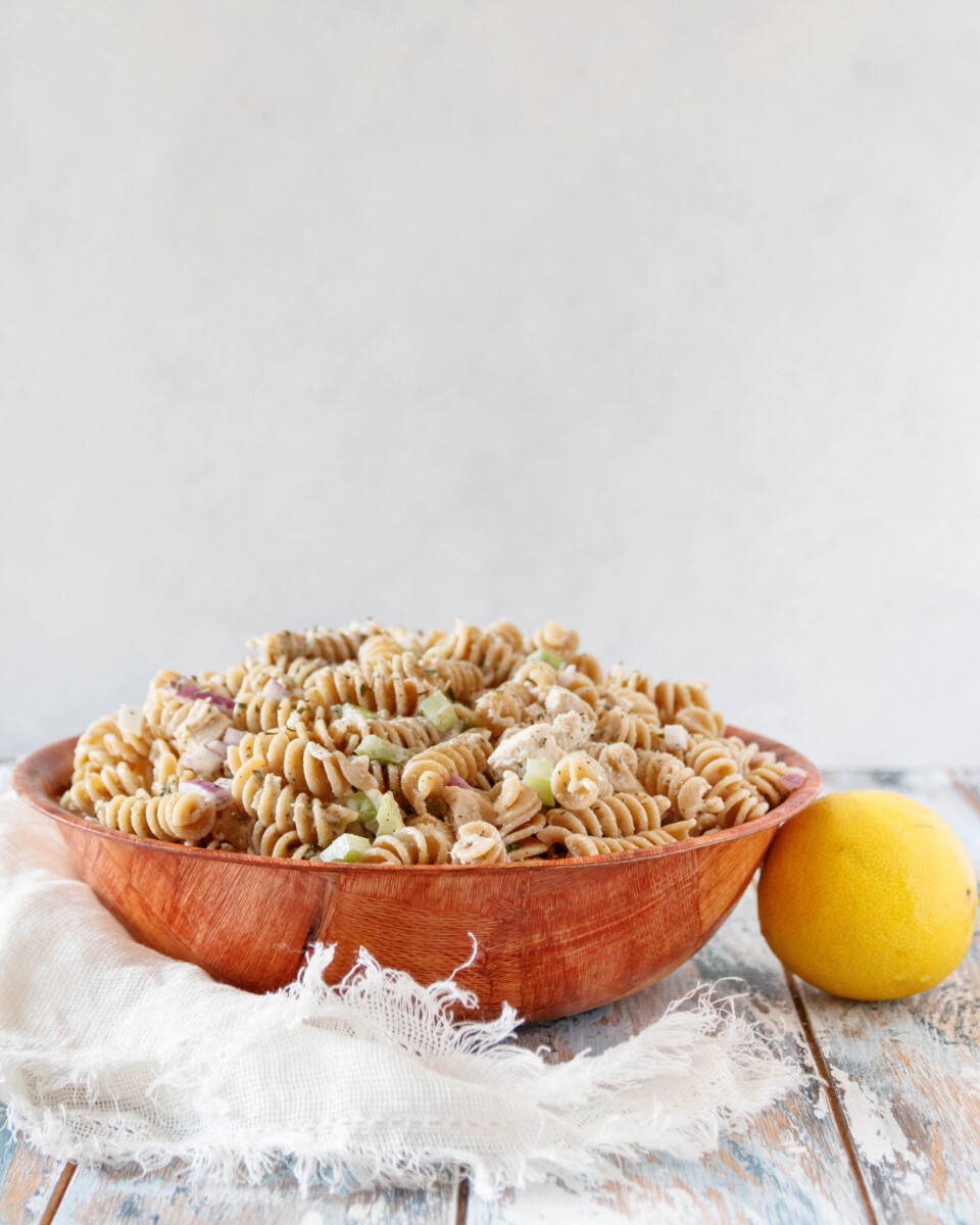 creamy lemon chicken pasta salad in a wooden bowl