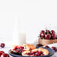 a cherry hand pie cut in half on a small black matte dessert plate. There's a bowl of fresh cherries and a small jug of milk in the background. White weathered tabletop and bright white background