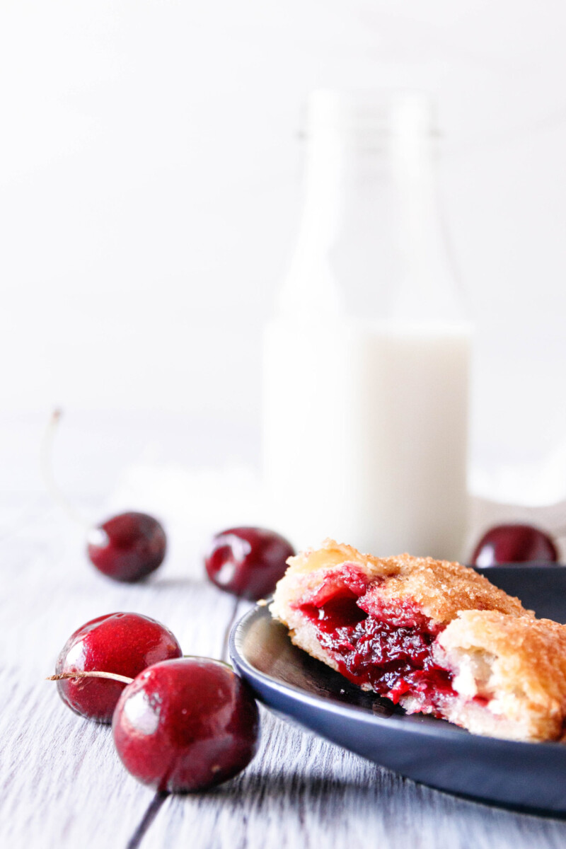 side-view close up of the cut cherry hand pie to highlight the pie to filling ratio. Fresh cherries are scattered around the plate and a small milk jug can be seen in the background