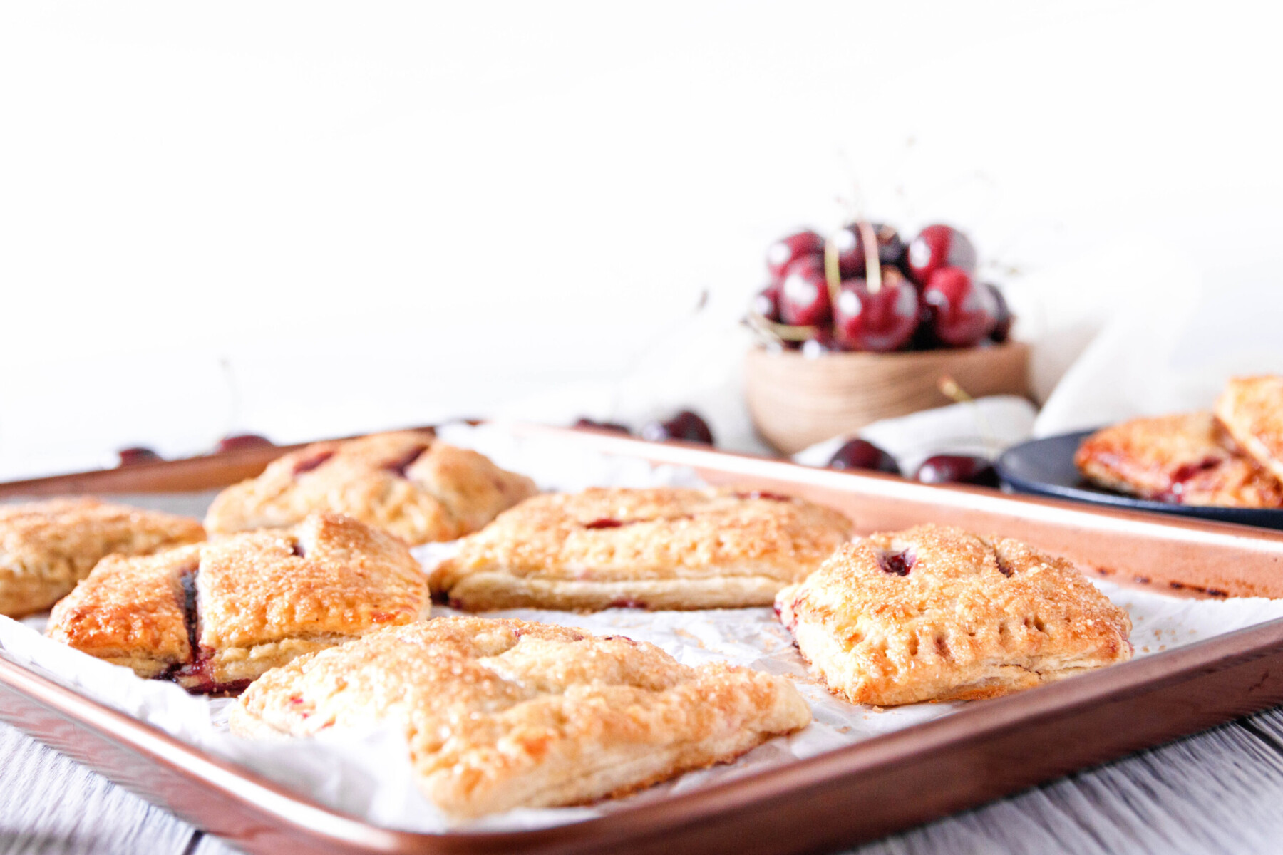 classic cherry hand pies fresh out of the oven resting on a baking sheet