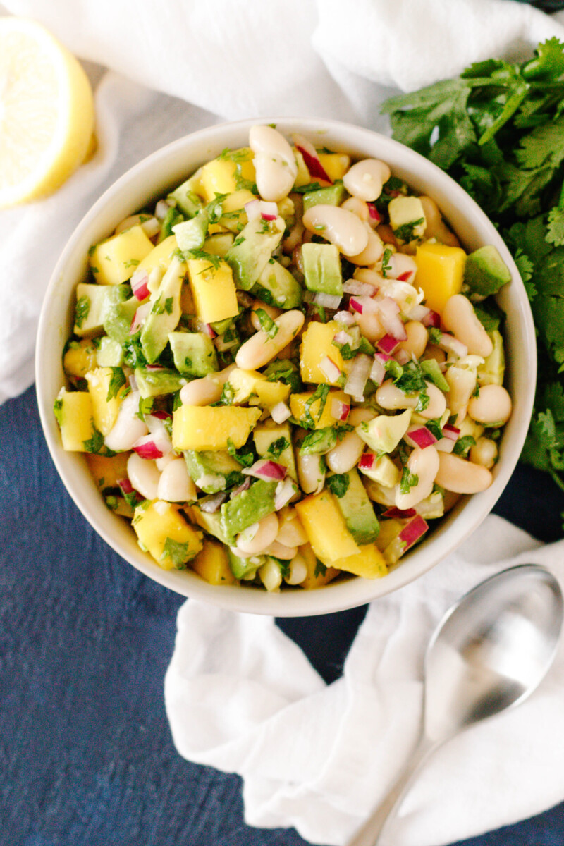 overhead photo of the mango avocado salad in a serving bowl, surrounded by a napkin, some fresh cilantro, half a lemon wedge and a matte-finish serving spoon