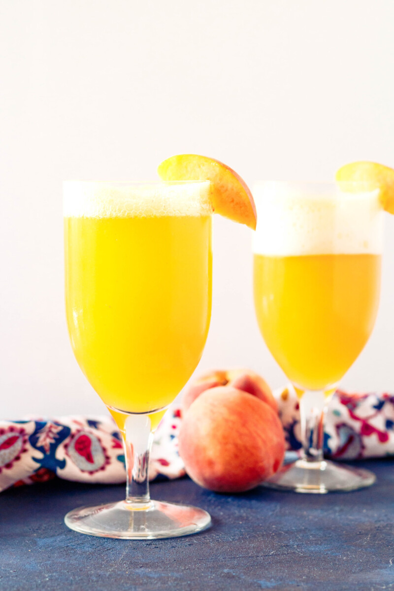two peach shandy beer cocktails on a blue tabletop with a white background and slice of peach garnishing each glass