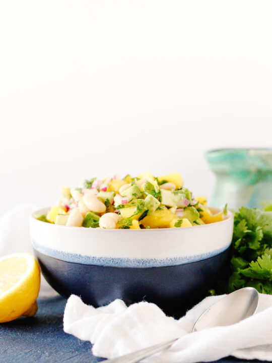 easy mango avocado salad in a white and blue bowl sitting on a blue tabletop with a white background.