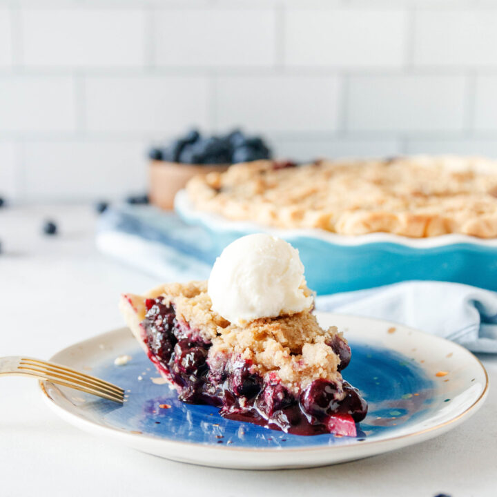 slice of blueberry pie on a plate with a scoop of vanilla ice cream on top