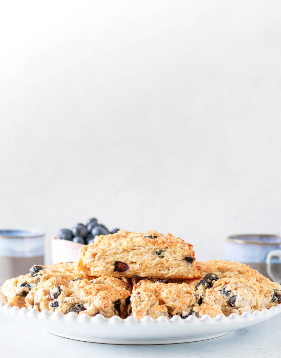 Scones made with the blueberry scone recipe piled on a white serving plate. A white background and pink bowl of fresh blueberries are in the rear of the shot