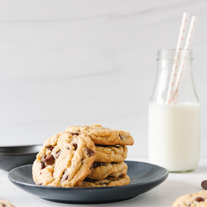 stacked chai chocolate chip cookies on a black plate with a bottle of milk with two straws in the background