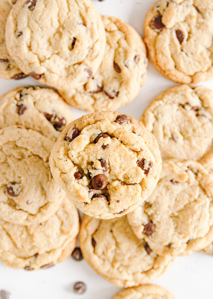 """top view of baked chai chocolate chip cookies with one cookie in focus and closer to the lens to look like it's """"hovering"""" over the others in the background"""