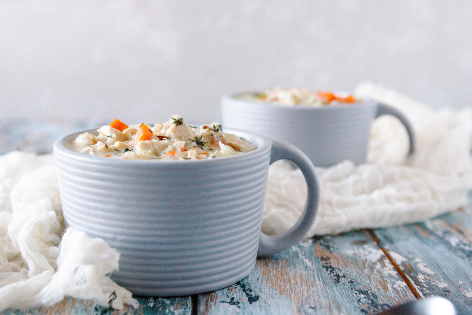 horizontal image showing two bowls of soup on a blue mottled tabletop with a grey background