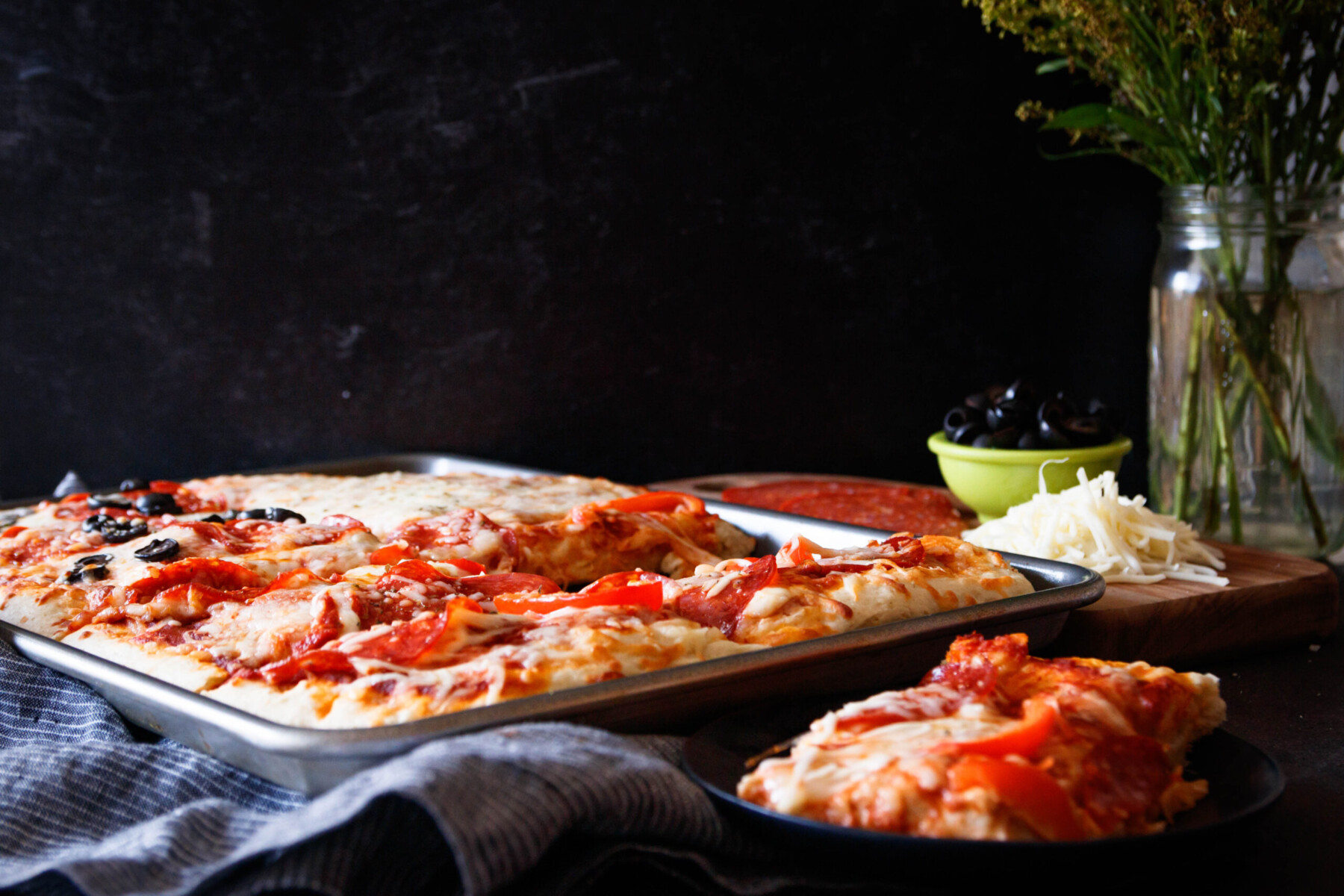 horizontal image of the pizza. There's a served slice of pizza in the foreground of the image on a small black plate.
