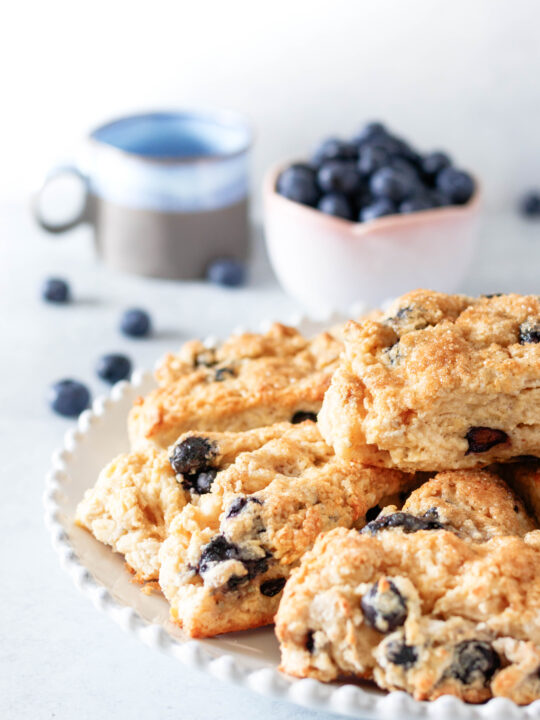 Angled top view of the scones piled on a plate with fresh blueberries and a grey and blue glazed coffee cup in the background