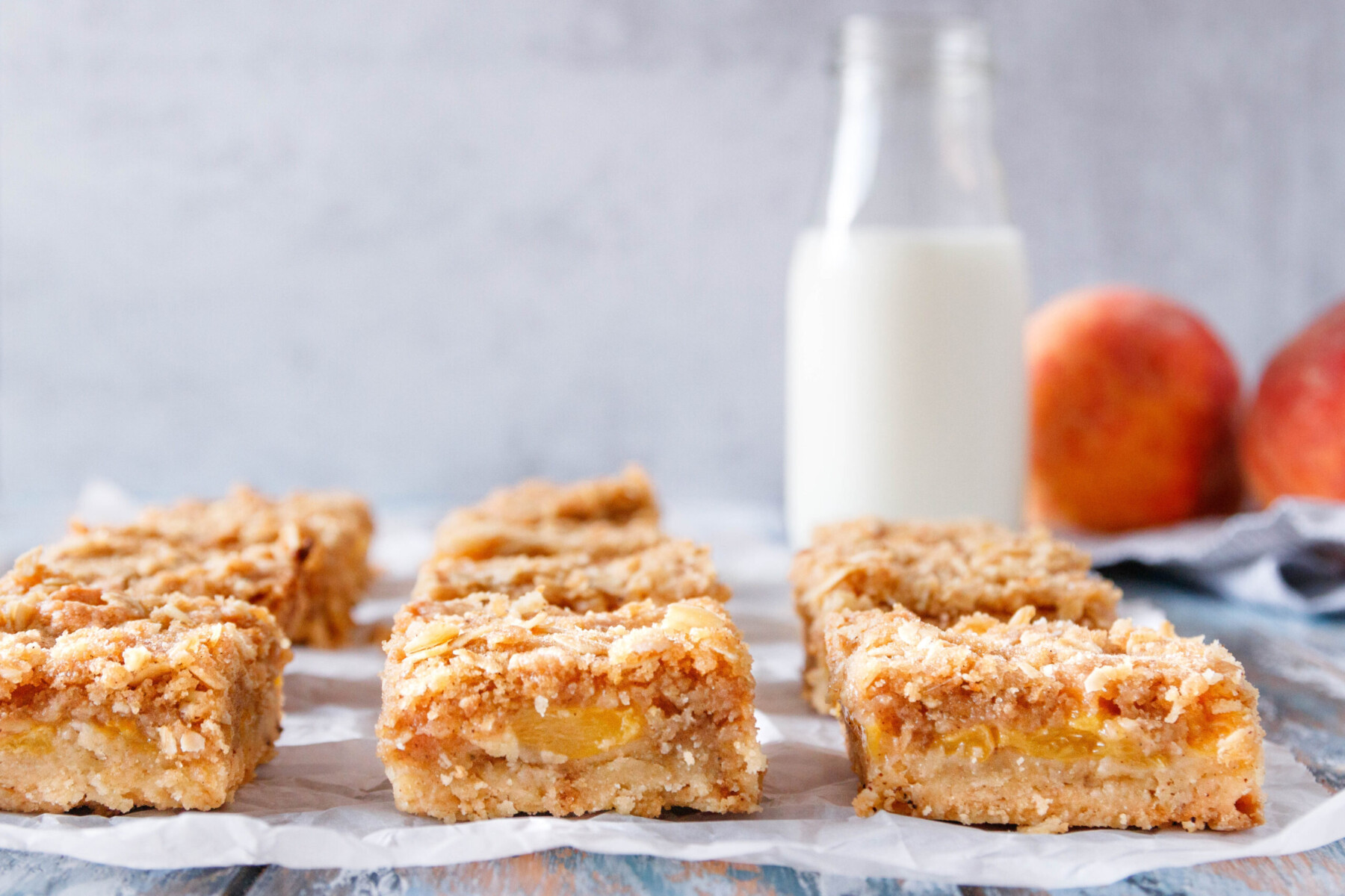 close up of the bars arranged in a single layer and sliced so you can see the base, peach, and crumb layers
