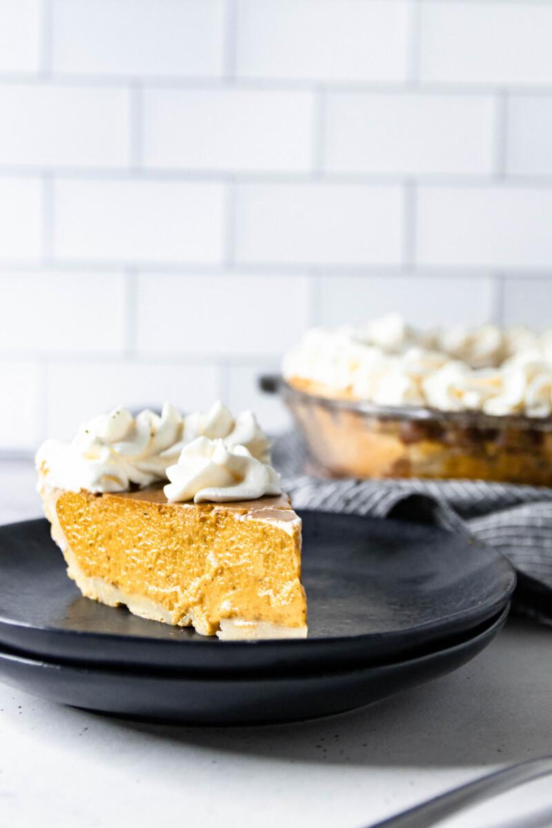 angled image of a slice of pumpkin pie served on a matte black dessert plate