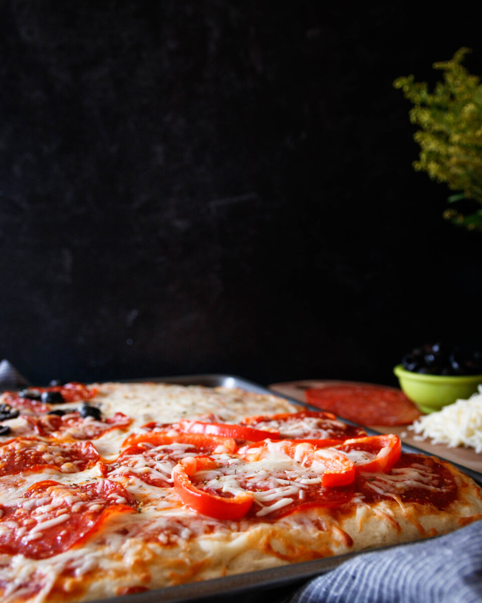 baked pizza resting in the pan on a table with olives and pepperoni in the background. Black backdrop.