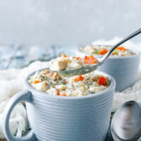 spoon lifting out of a soup mug filled with the turkey and wild rice soup