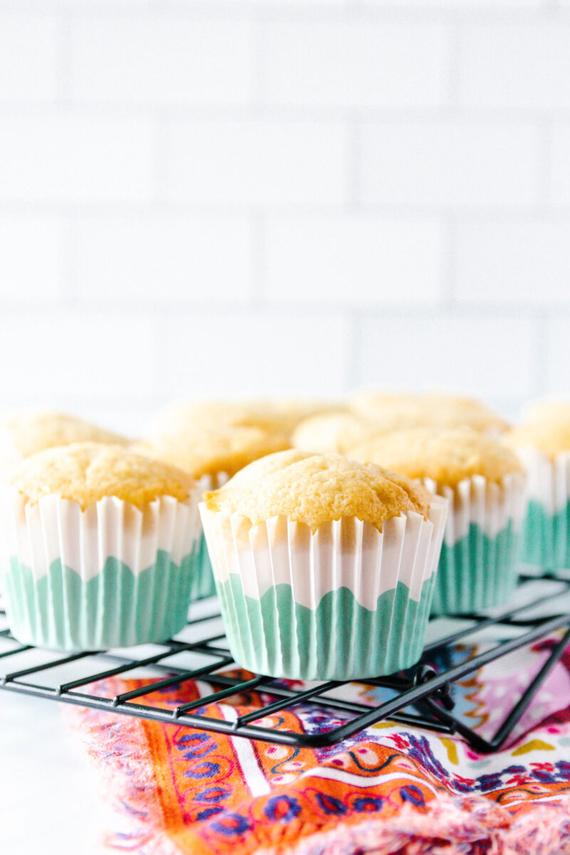 baked vanilla cupcakes cooling on a rack