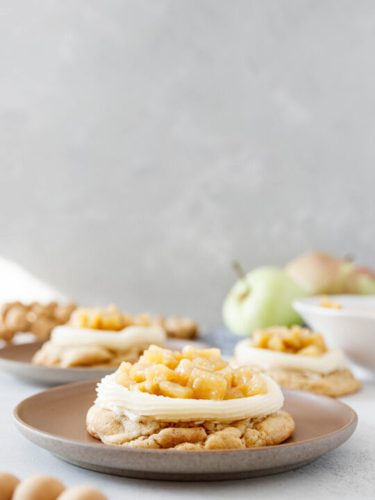 iced apple cookies, fully frosted and topped on individual dessert plants for serving. Grey background